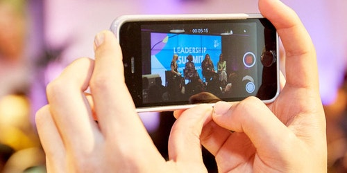 a head holding a iphone and recording on the phone of leadership summit speaking panel