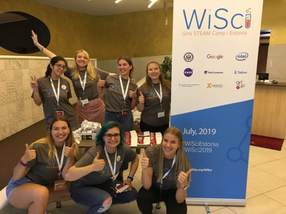 7 girls take group pictures with the WiSci girl STEAM camp standing poster