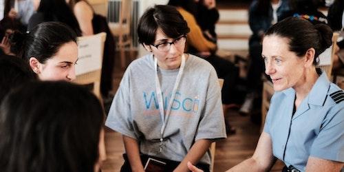 一名女性正在和 3 名 Girl Up 女孩聊天,照片中的女孩都穿着印有 WiSci 的 T 恤,位于中间的是往届青年顾问成员 Becca Bean,她正在专心聆听谈话