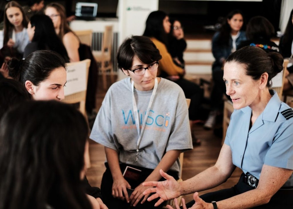 a woman is talking with 3 girl up girls in the pictures and the girls are wearing WiSci t-shirt in the centre is Becca Bean Teen Advisor Alumna and playing attention to the conversation