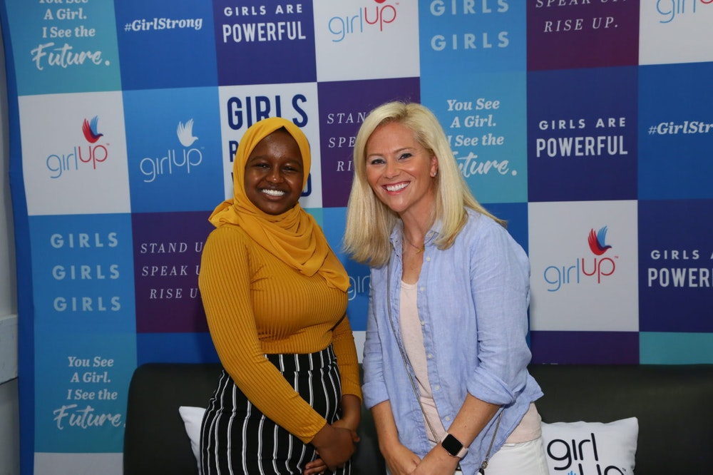 Munira Alimire taking picture with a speaker in front of the girl up borad