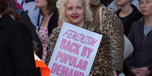 "a woman holding a sign ""Feminism back by popular demand"""