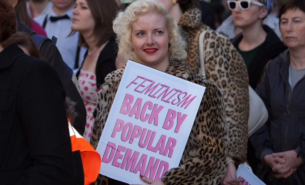"""a woman holding a sign """"Feminism back by popular demand"""""""