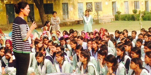 a woman standing and speaking in front of a group of girl students who are sitting on the group listen to her at the school