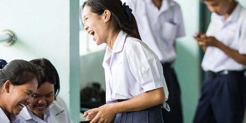 两名女孩坐着,一边看手机一边笑,另一名女孩站着,手里拿着手机在笑(在模糊的背景中,两名男孩也拿着手机)