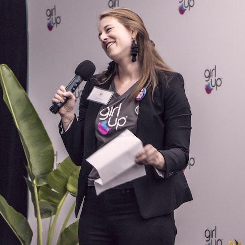 Bailey Leuschen, diretora de programas e impacto, segurando um microfone e sorrindo no palco. Ela está usando a camiseta da Girl Up