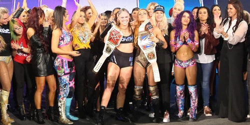 a group of WWE women clapping for the winner on the stage