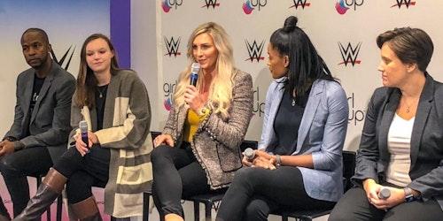 Fórum WWE e Girl Up (5 pessoas no palco). A superstar da WWE, Charlotte, está segurando um microfone e olhando para a frente