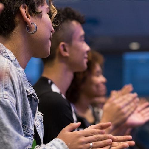 Adolescentes sentadas, sorrindo e batendo palmas