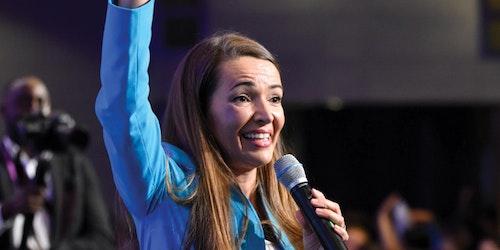 Julie Carrier levant la main droite en parlant dans un microphone qu'elle tient avec sa main gauche