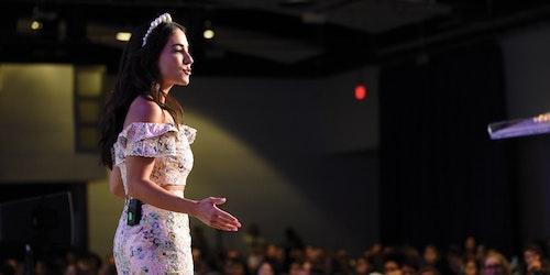 une fille portant une robe blanche, le bras ouvert et s'adressant à la foule (montrant son visage de profil)