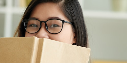 a girl with a book cover her lower face with her glasses on