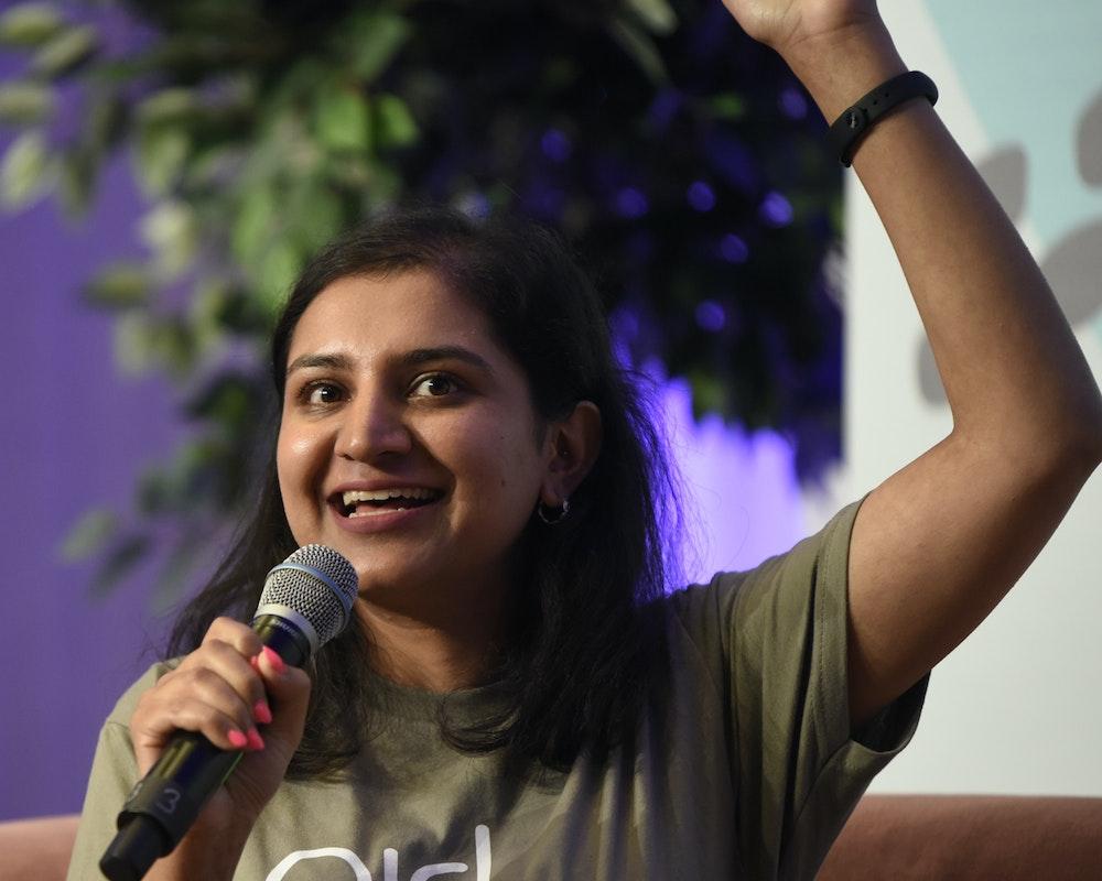 Una chica sostiene un micrófono y levanta su mano izquierda.