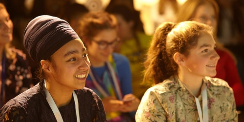 two Girl Up members in Europe from different ethnic backgrounds smiling and together at the event listening to the speaker (close shot)