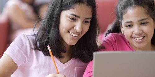 Duas meninas sorridentes fazendo anotações e dividindo um laptop