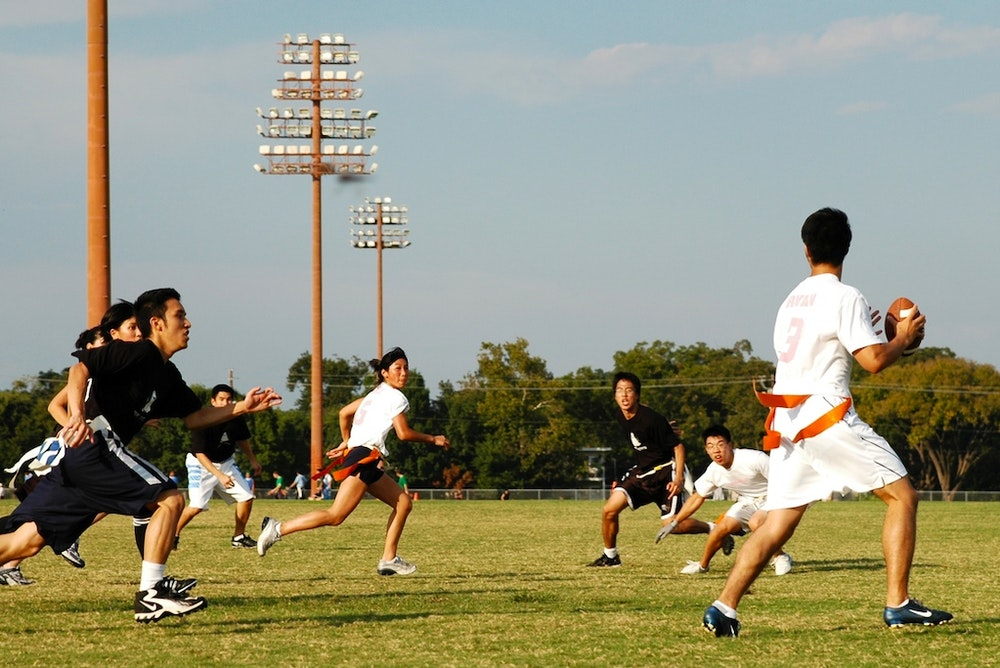 a group of girls playing Flagfootball with boys