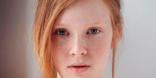 Foto em close muito próximo de uma menina loira olhando diretamente para a câmera