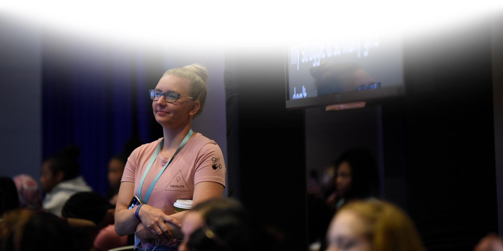Uma menina em pé, no meio da plateia, sorrindo e ouvindo o conferencista do evento