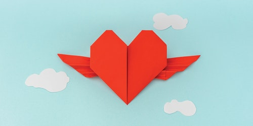 Un corazón de papel plegado con alas.
