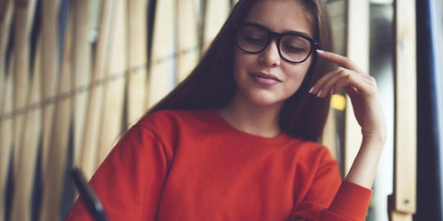 (lower angle) a girl wearing black glasses and writing on her note book