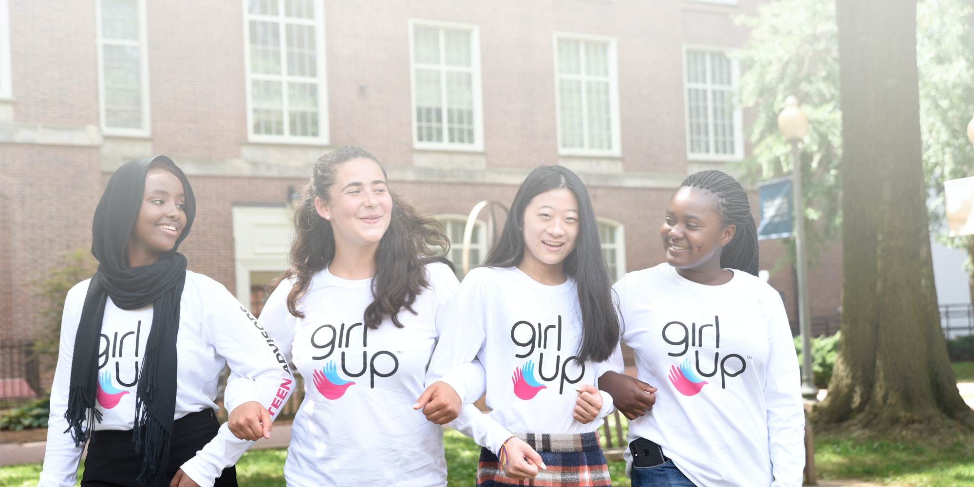 4 different ethnic Girl Up girls with the girl up shirt on (group picture)