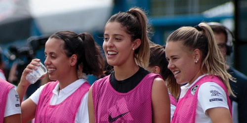 a group of soccer player laughing and looking straight with their uniform