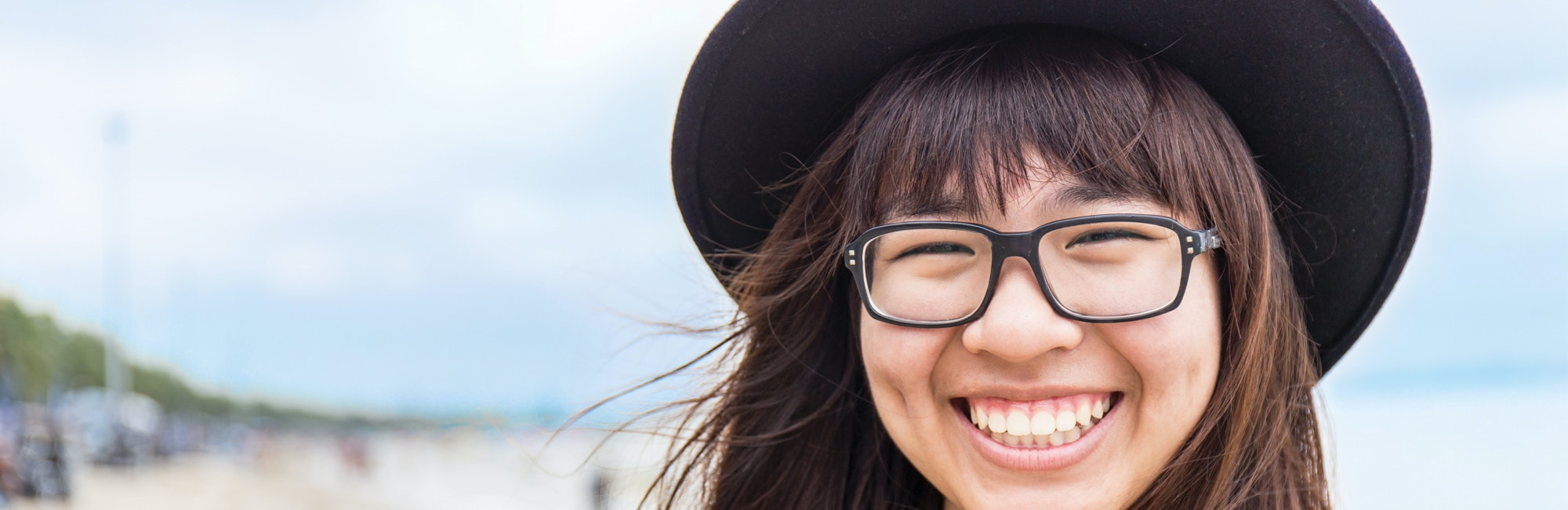 a close up shot of a girl with big smile and wear hat with glasses on