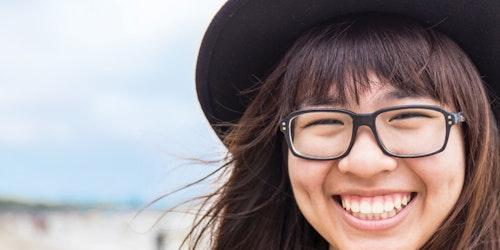Foto em close muito perto de uma menina sorridente, usando chapéu e óculos