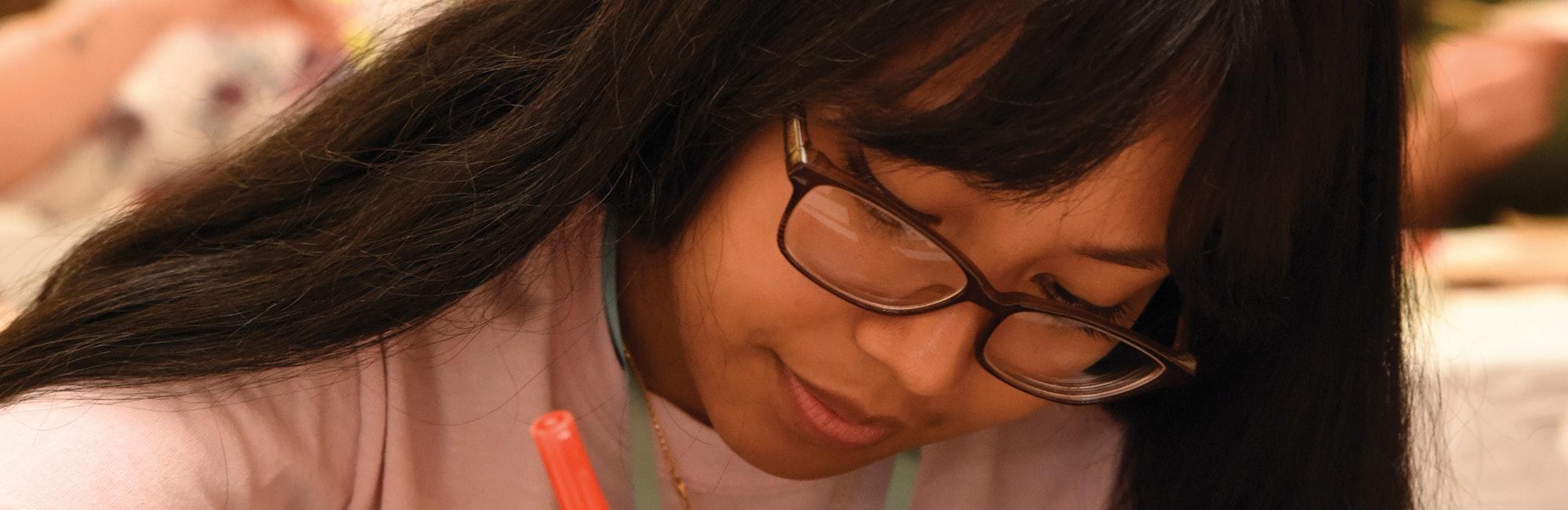 Foto em close muito próximo, cortada, de uma menina asiática de óculos olhando para baixo