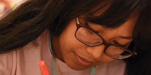 a very close cutoff shot of a Asian girl with glasses looking down and holding a pan