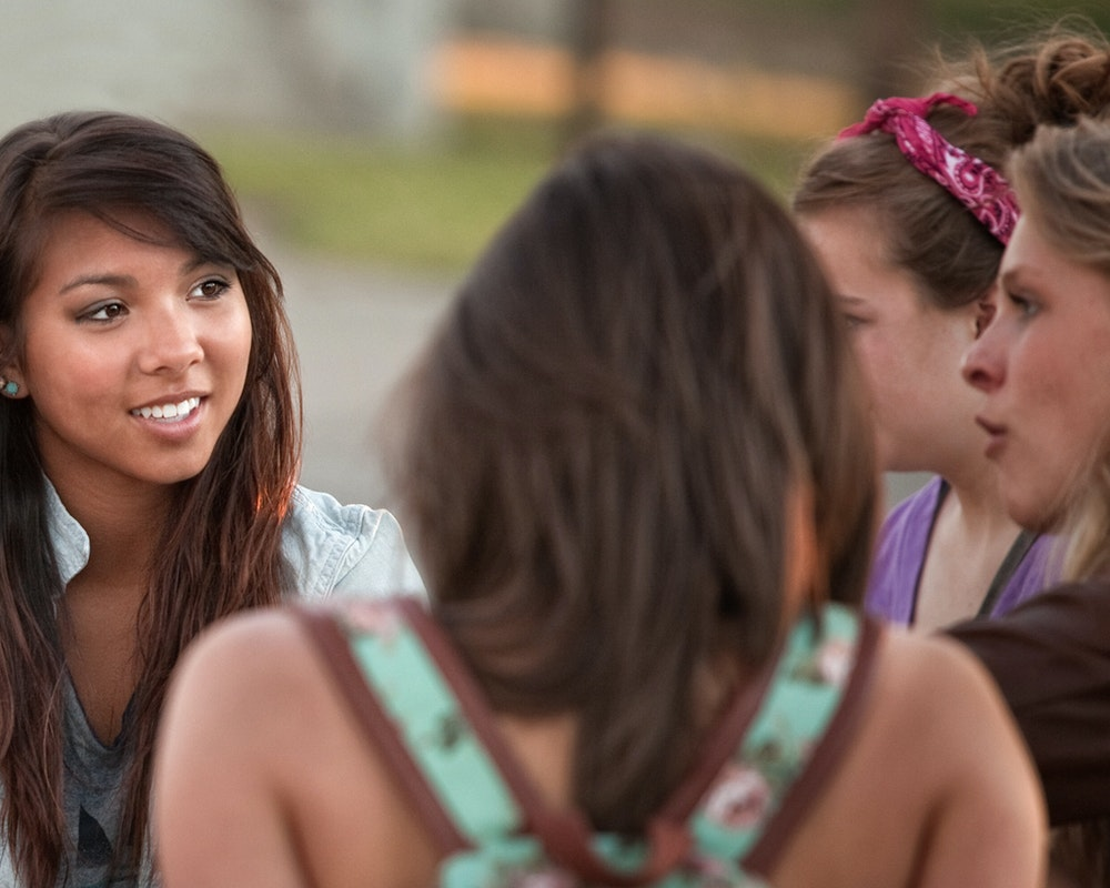 a group of girls talking in a circle, looking at each other (close shot)