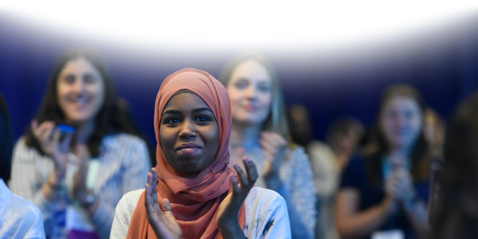 一名女孩戴着粉色头巾,面带微笑拍手