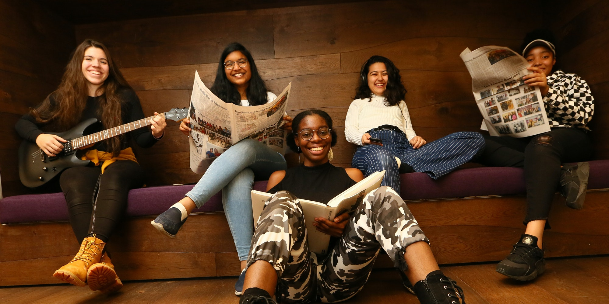 5 different ethnic girls in the picture holding books (sitting on the front floor) and holding guitar and newspaper (sitting on the back couch)