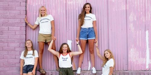 """Cinco meninas vestindo camisetas com a frase """"Girls support each other"""" (Meninas se ajudam), tendo um plano de fundo rosa"""