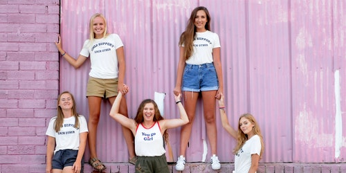 une photo de groupe (5 filles de Girl Up ) avec un maillot « girls support each other », arrière-plan rose