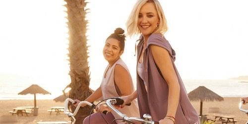 Kate Hudson et une autre fille souriant sur leur bicyclette, portant la ligne de vêtements «girl almighty» de Fabletics