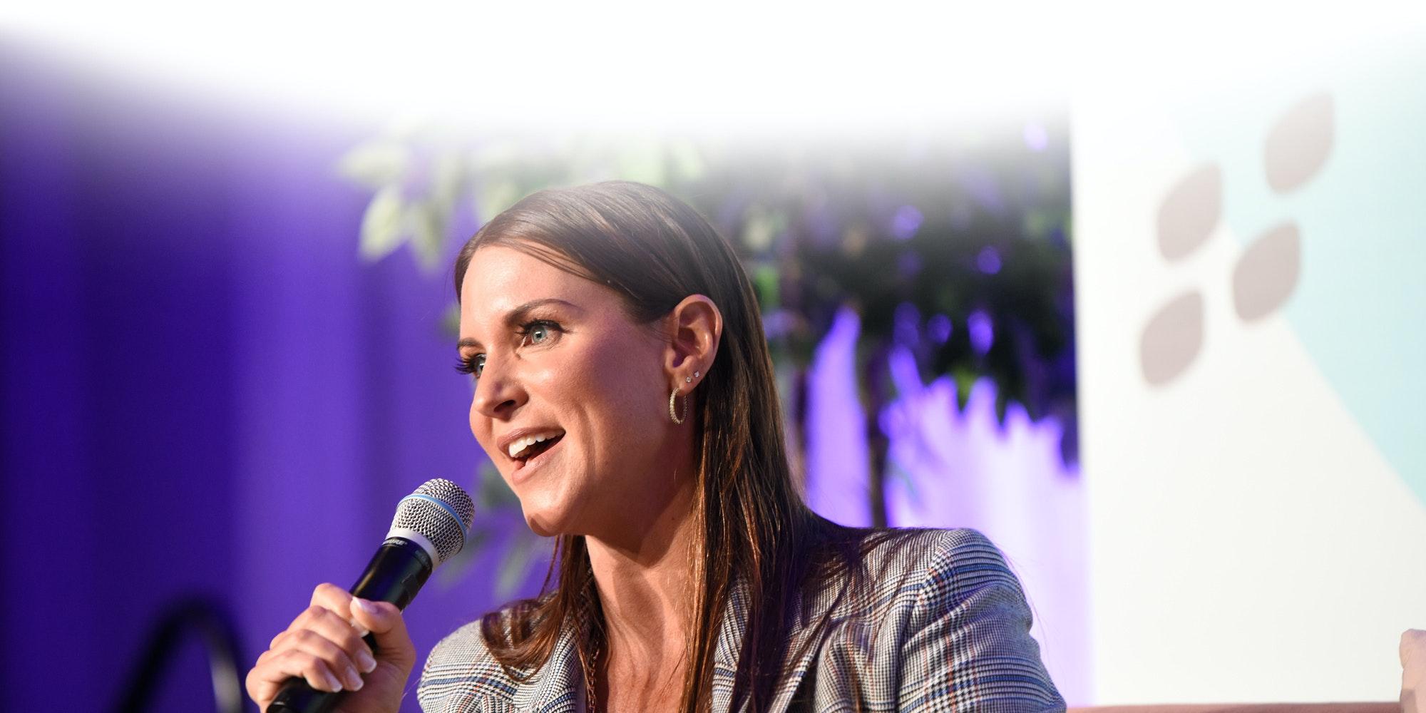 Foto de perfil de Stephanie McMahon, diretora executiva da WWE, segurando um microfone