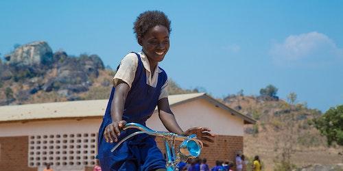 一名穿着蓝色连衣裙的女孩在骑自行车,脸上带着灿烂的微笑