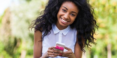 une fille tout sourire, regardant droit devant elle et tenant son iPhone
