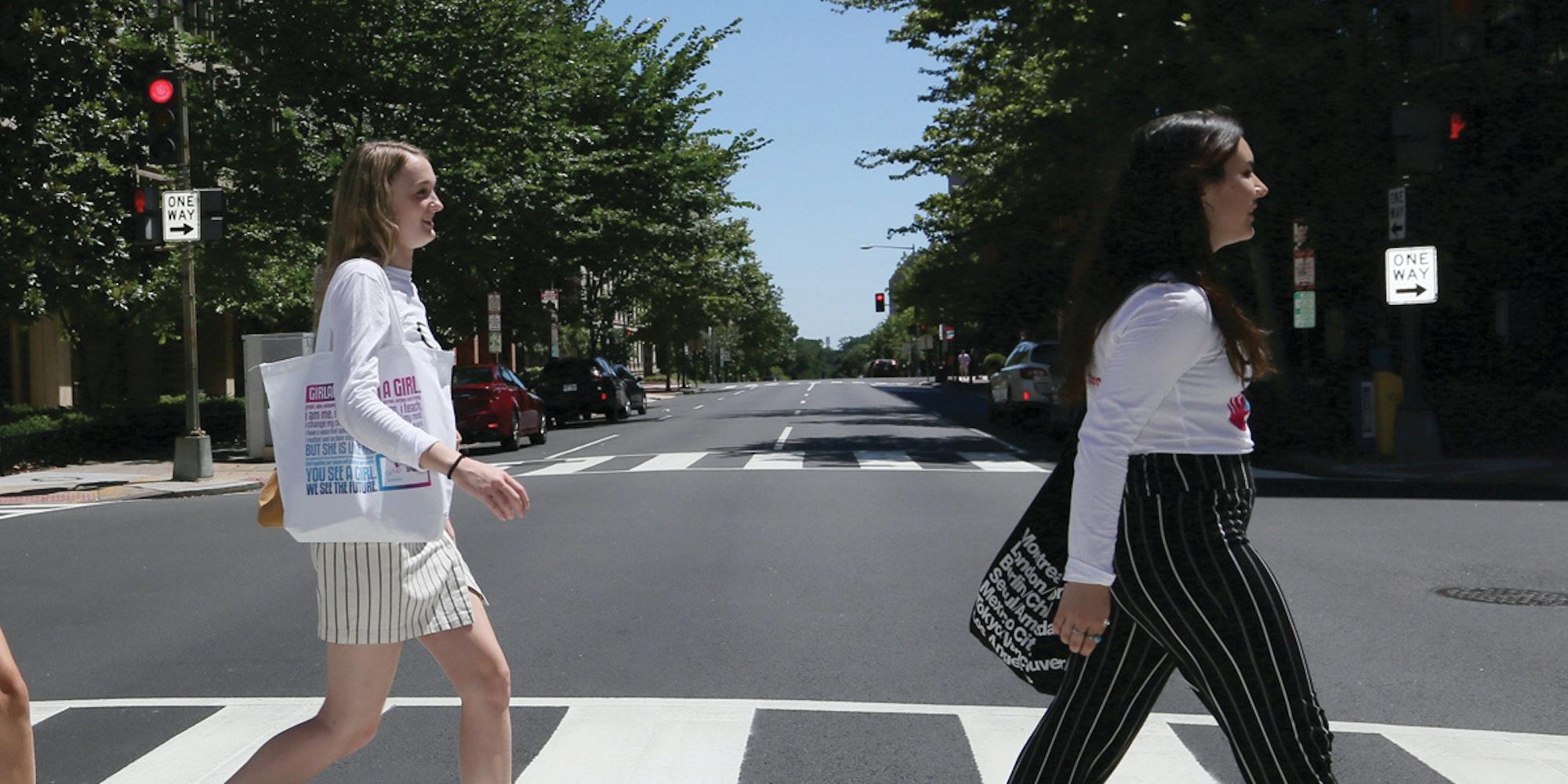 5 名女孩穿着青年顾问 T 恤,面朝前方一个接一个地过马路
