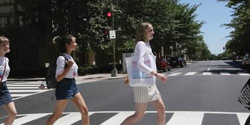 Meninas atravessando a rua em fila, olhando para frente e usando a camiseta de consultora adolescente