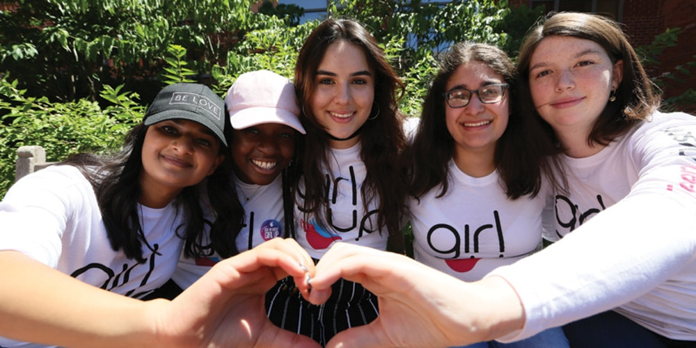 5 teen advisors girl have their hand around each other back and use their hand to make a heart hand shape