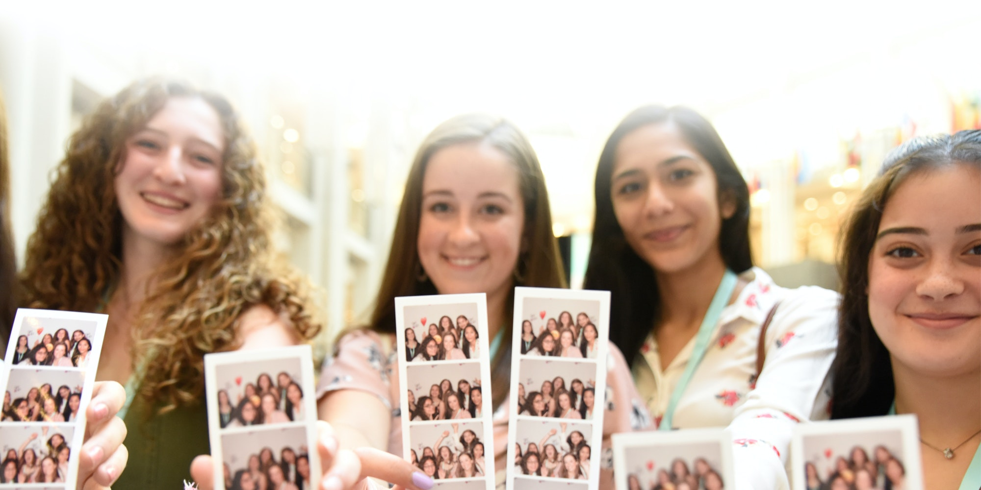 5 girls holding their photo booth pictures to the camera in the leadership summit