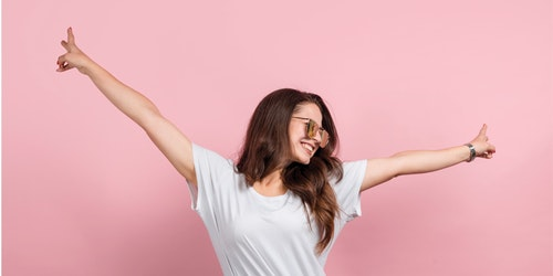 a girl with two of her arm wide open posing victory sign and big smile with pink background