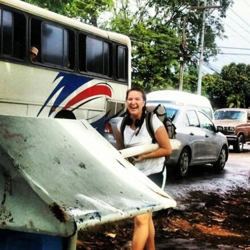 Foto da auxiliar sênior dos programas WiSci (com uma mochila e fones de ouvido) sorridente em pé ao lado de um ônibus